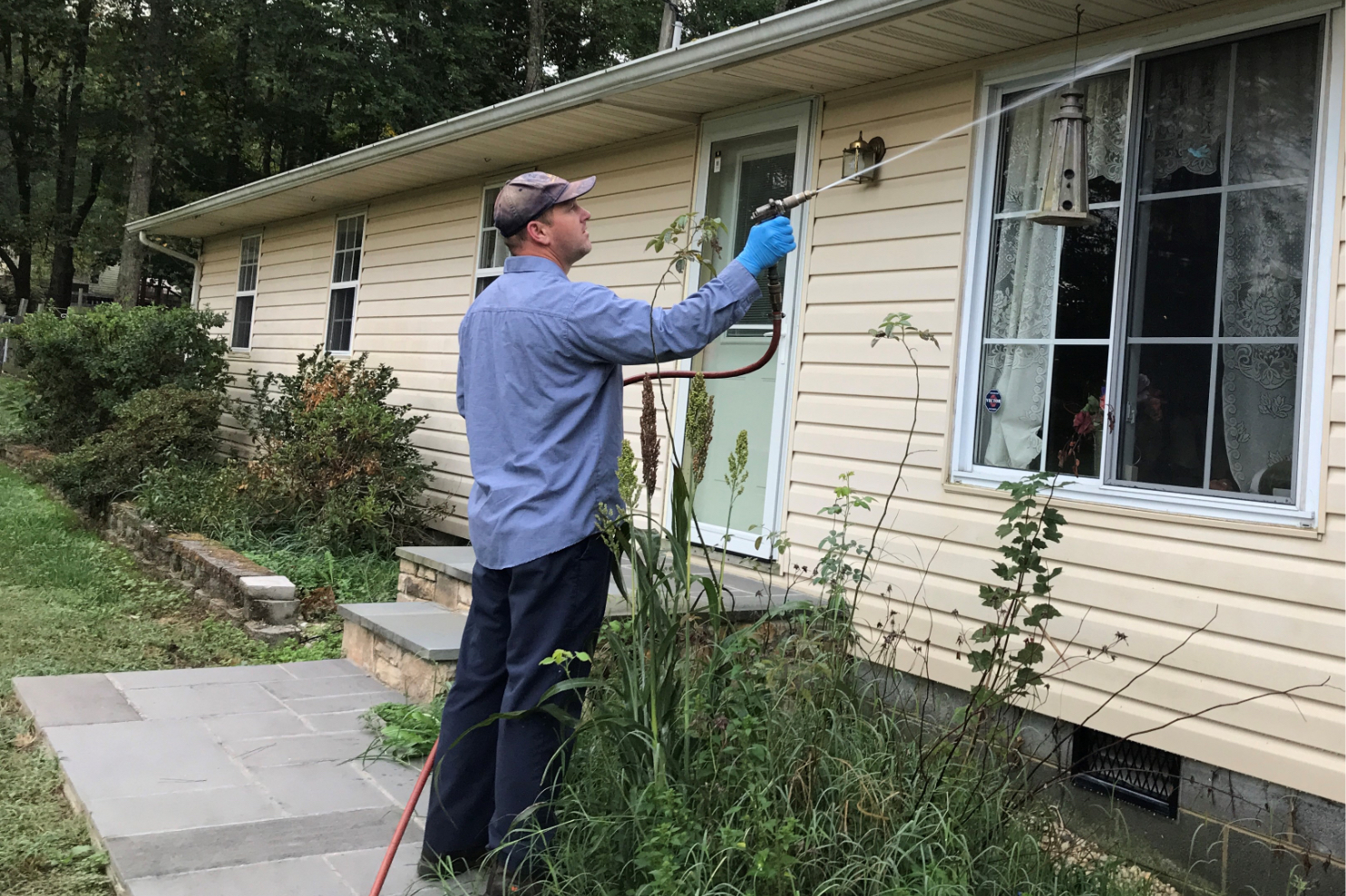 Photo of a technician treating a house exterior