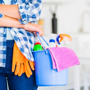 woman holding bucket with cleaning supplies