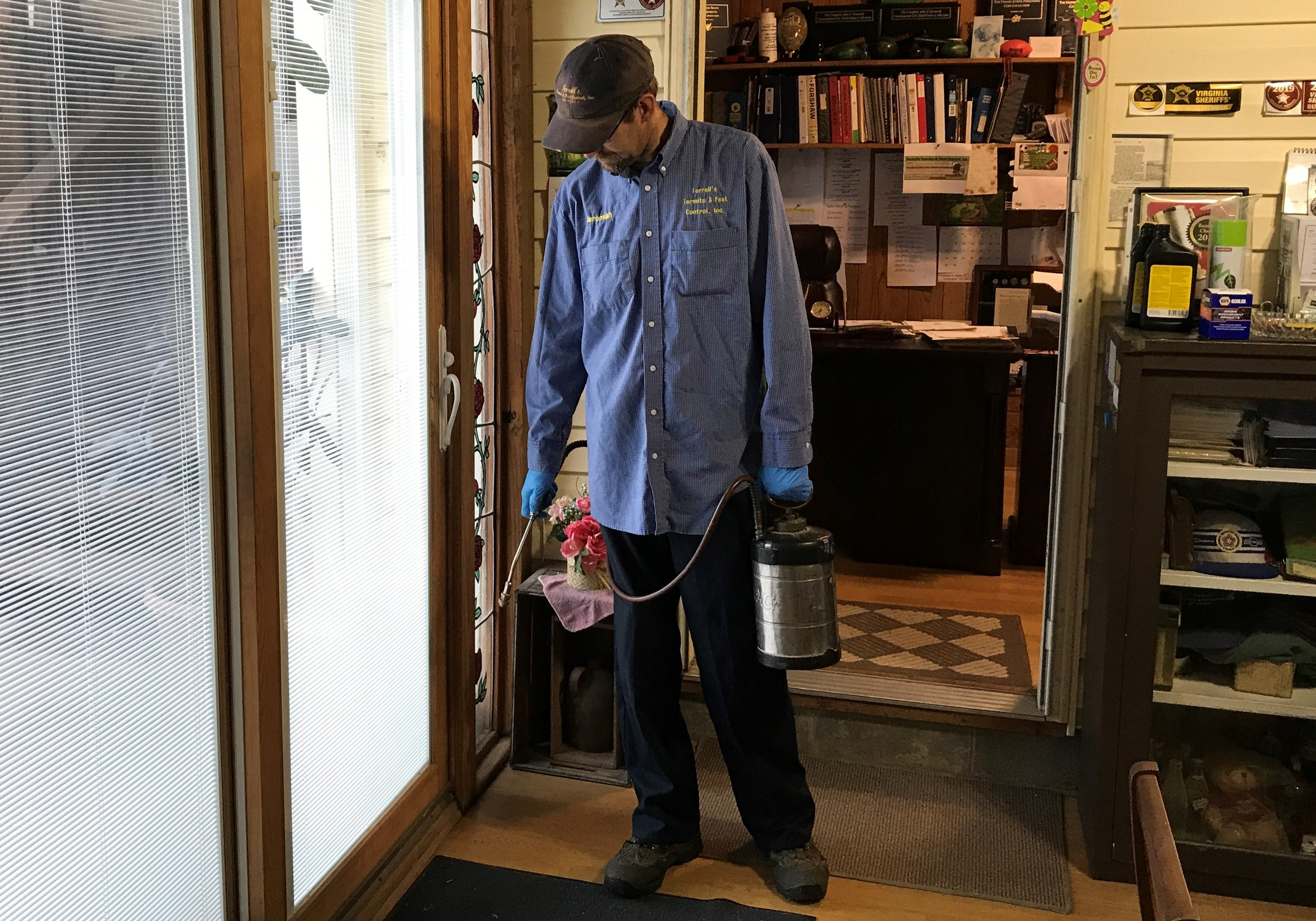Pest control technician spraying for insects